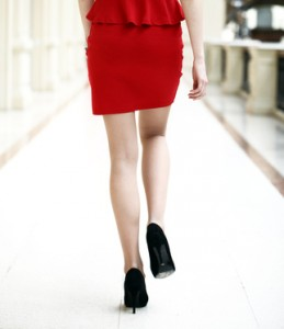 Beautiful female legs walking indoor, red dress close up